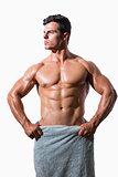 Shirtless muscular man wrapped in white towel
