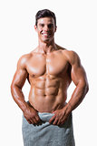 Smiling shirtless muscular man wrapped in white towel