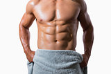 Mid section of a shirtless muscular man wrapped in towel