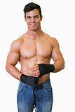 Shirtless muscular man binds bandage on his hand