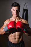 Shirtless muscular boxer in defensive stance