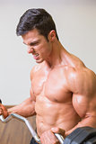 Shirtless muscular man lifting barbell in gym