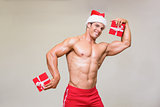 Shirtless macho man in santa hat holding gifts