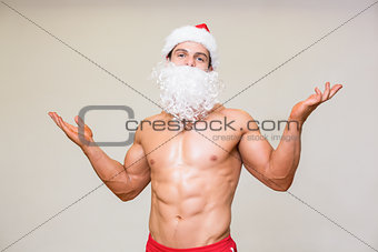 Portrait of shirtless macho man with fake santa beard