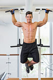 Shirtless male body builder doing pull ups