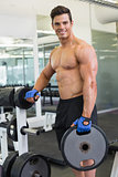 Shirtless muscular man lifting weight in gym