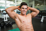 Smiling shirtless muscular man in gym