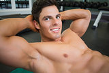 Smiling muscular man doing abdominal crunches