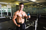 Muscular man holding energy drink in gym