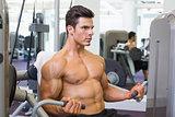 Determined muscular man working on abdominal machine