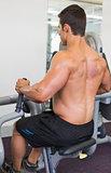 Muscular man working on abdominal machine at the gym