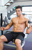 Muscular man working on abdominal machine at the gym