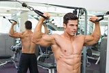 Shirtless muscular man using resistance band in gym
