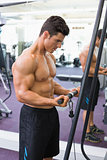 Shirtless muscular man using triceps pull down in gym