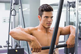 Shirtless muscular man using biceps pull up in gym