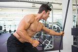 Shirtless muscular man using resistance band in gym