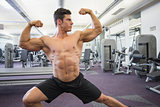 Shirtless muscular man flexing muscles in gym