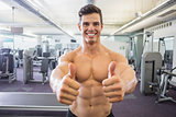 Smiling muscular man giving thumbs up in gym