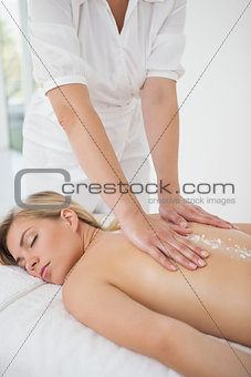 Beautiful blonde enjoying a salt scrub treatment