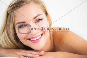Beautiful blonde lying on massage table smiling at camera