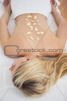Beautiful blonde lying on massage table with petals on back