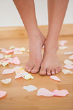 Womans feet standing around rose petals