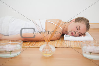 Beautiful blonde relaxing on bamboo mat