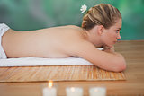Peaceful blonde lying on bamboo mat