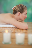 Peaceful blonde lying on bamboo mat