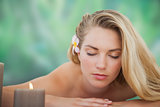 Peaceful blonde lying on towel with candle
