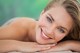 Peaceful blonde lying on towel smiling at camera