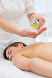 Woman getting massage oil on her back at spa center