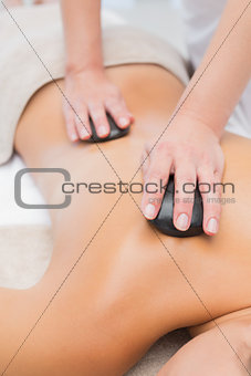 Beautiful woman receiving stone massage at spa center