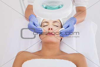 Hands cleaning woman\'s face with cotton swabs