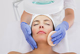 Hands cleaning woman's face with cotton swab