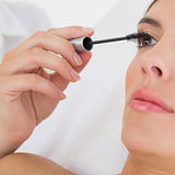 Hand applying mascara to beautiful woman