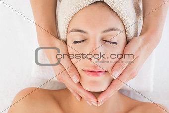 Attractive woman receiving facial massage at spa center