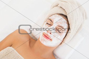 Attractive woman having white cream on her face at spa center