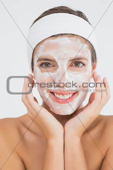 Attractive woman having white cream on her face