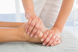 Woman receiving leg massage at spa center