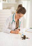 Doctor woman writing in prescription