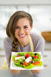 Portrait of smiling young housewife showing greek salad