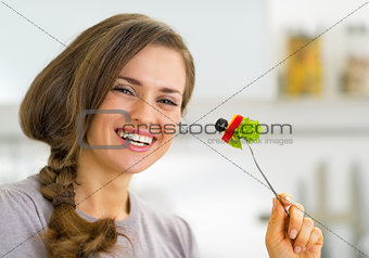 Portrait of smiling young housewife eating vegetables