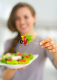 Closeup on young housewife giving fork with vegetables