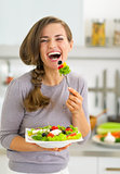 Happy young woman eating greek salad in kitchen