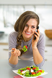 Happy young woman eating greek salad in kitchen and talking cell