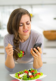 Young woman eating in kitchen and writing sms