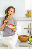 Happy young woman eating greek salad in modern kitchen
