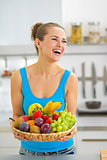 Smiling young woman with fruits plate in kitchen