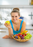 Happy young woman with fruits plate eating apple